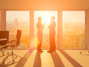 Silhouettes of two business men talking in front of a window inside a contemporary office with a conference desk, while warm sunset light fills the room creating lens flares. Outside the windows the skyline of a city with skyscrapers is visible.